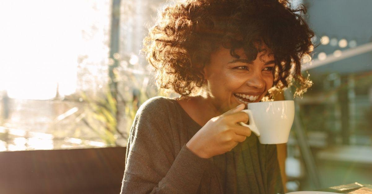 woman with mug inside smiling